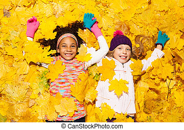 African and Caucasian girl covered in maple leaves