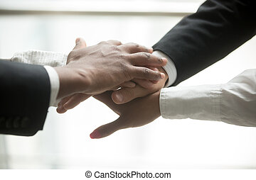 African and caucasian partners put hands together, close up view