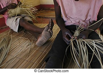artisan - African artisan produces straw hats...