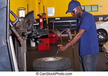 mechanic pumping car tyre