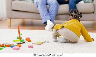 african baby girl playing with toy blocks at home - ...