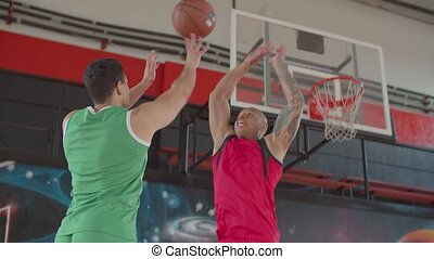 African american basketball defender blocking shot of opposing player during game on indoor court. Defensive player legally deflecting field goal attempt from offensive player to prevent score.