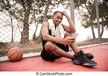 African basketball player chatting and listening music