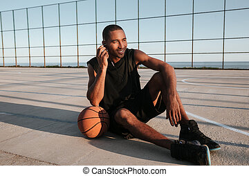 African basketball player sitting at the playground and listening music