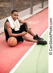 African basketball player sitting in the park and holding tablet