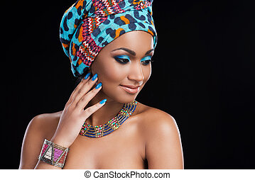 African beauty. Beautiful African woman wearing a headscarf and necklace and looking away while standing against black background