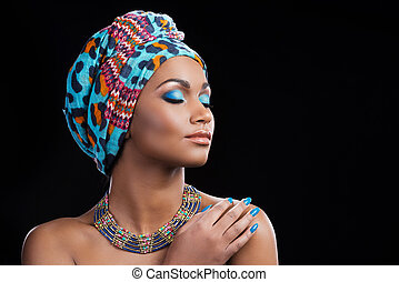 African beauty. Beautiful African woman wearing a headscarf and necklace keeping eyes closed while standing against black background