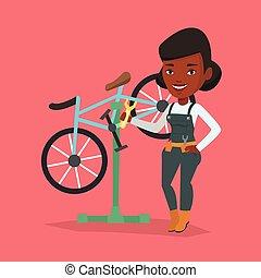 African bicycle mechanic working in repair shop.