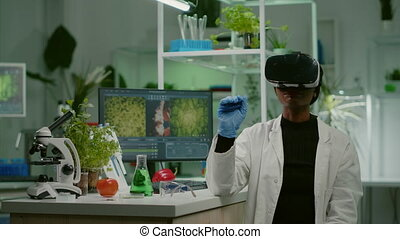 African biologist researcher with virtual reality headset researching new genetic experiment for microbiology expertise. Medical team working in pharmaceutical laboratory analyzing dna test