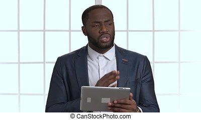 African black business man in suit talking holding tablet. Indoor, checkered windows background.