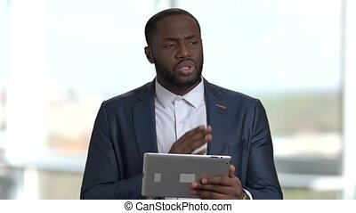 African black man with tablet speaking at business seminar....
