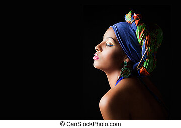 African black young woman beauty portrait with colorful turban headscarf profile studio shot on black