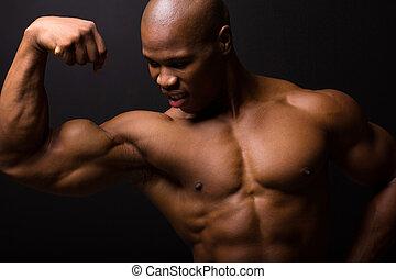 african bodybuilder on black background - african muscular...