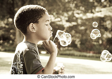 bubbles - african boy blowing bubbles in park