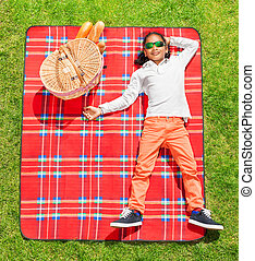 African boy in sunglasses relaxing on the picnic
