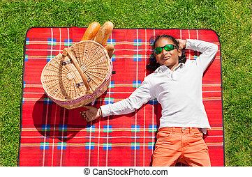 African boy relaxing on grassy meadow in summer