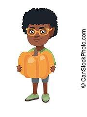 African boy standing with a big orange pumpkin.