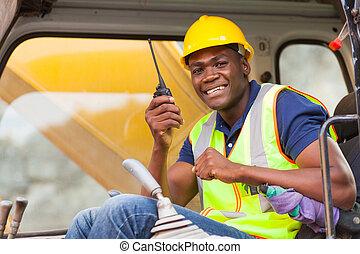 african bulldozer operator talking on walkie talkie