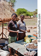 two African street vendors selling local products