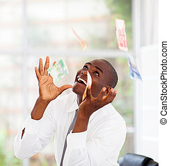 african businessman catching money falling from above
