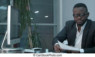 African Businessman doing paper work, calculating finance bills in office