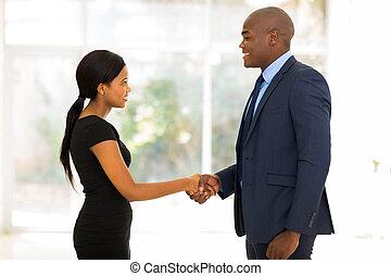 african businessman handshaking with young businesswoman