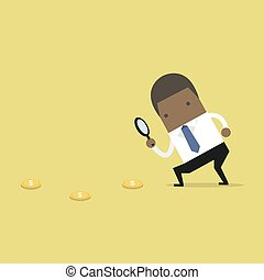 African businessman holding a magnifying glass follow dollar coins.