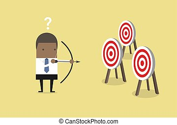 African businessman holding bow and arrow confused by multiple bulls eye target.