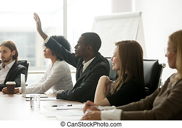 African businessman raising hand asking question at diverse team