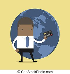 African businessman standing holding his a credit card in front of the globe.