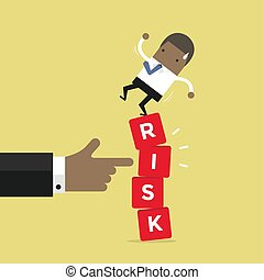 African businessman standing on shaky risk blocks by hand of manager.