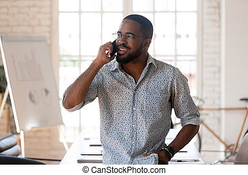 African businessman talking on phone inside of modern office