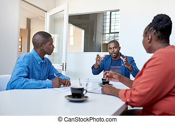 African businessman talking with colleagues in a modern office