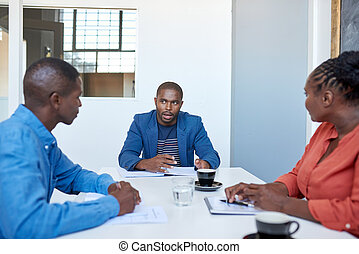 African businessman talking with coworkers in a modern office