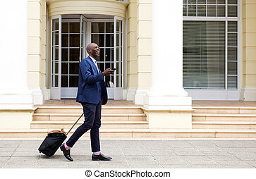 African businessman walking with bag and mobile phone