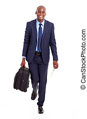 african businessman walking with suitcase