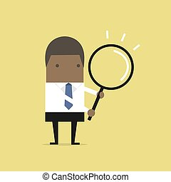 African businessman with a magnifying glass.