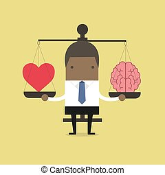 African businessman with Heart and brain on scales.