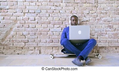 African businessman with laptop and headphones. - Handsome...
