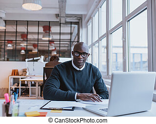 African businessman working in modern office