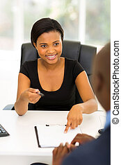 african businesswoman giving her business partner a contract
