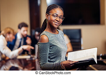 African businesswoman look at camera in boardroom with colleagues in background