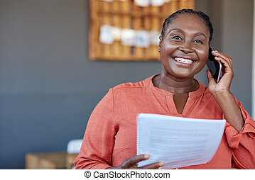 African businesswoman using a cellphone and reading documents at work