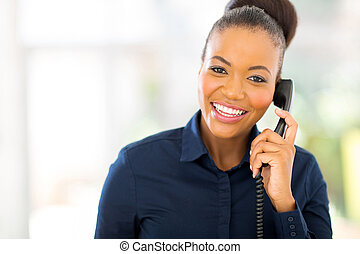 african businesswoman using landline phone - attractive...