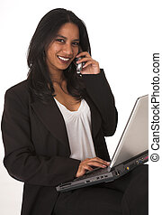 Young adult African-Indian businesswoman in casual office outfit sitting with a notebook computer on her lap on a typist chair on a white background. Not Isolated