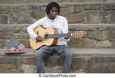 African busker playing guitar - African busker in Howick,...