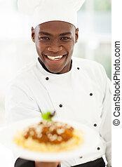 African chef in hotel kitchen presenting pasta