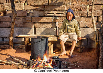 African child cooking in the summer kitchen