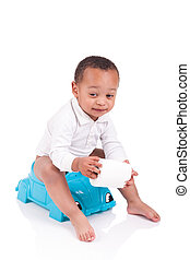 African child on potty play with toilet paper, isolated over whi