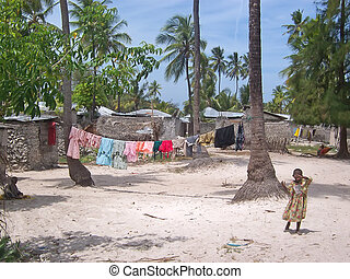African children with coloured tissus drying at the sun on a tropical beach village - Zanzibar - Tanzania.